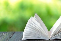 打开在木板条的书在抽象光 库存照片