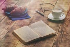 打开在木桌上的旧书用新月形面包和咖啡 免版税库存照片