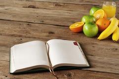 打开在木桌上的笔记本用果子和橙汁 库存图片