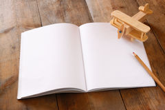 打开在木桌的空白的笔记本 为大模型准备 减速火箭的被过滤的图象 免版税库存图片