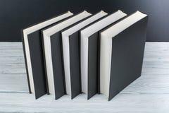 打开在木桌,黑委员会背景上的书 回到学校 教育产业概念 库存图片