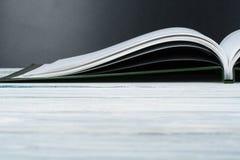 打开在木甲板桌和黑委员会背景上的书 回到学校 与拷贝空间的教育概念您的广告的 库存图片