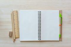 打开在木背景的笔记本与铅笔和统治者 库存图片