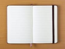 打开在木背景的笔记本 免版税库存图片
