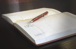 打开在桌上的笔记本和圆珠笔 免版税库存图片