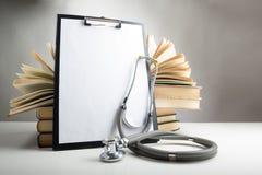 打开在桌上的精装书书,有空白的p的医疗剪贴板 免版税库存图片