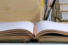 打开在桌背景和课本堆积的精装书 库存照片