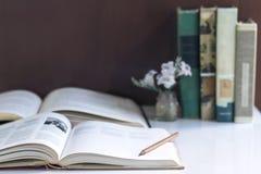 打开在桌背景和课本堆积的精装书 Sel 库存图片