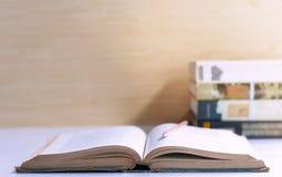 打开在棕色墙壁ba的桌上和课本堆积的精装书 库存图片