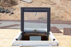 打开在沥青木瓦屋顶的塑料有双重斜坡屋顶的房屋或天窗窗口 免版税图库摄影
