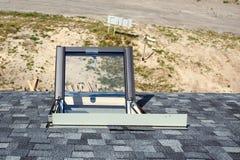 打开在沥青盖的屋顶的有双重斜坡屋顶的房屋的窗口天窗 免版税库存照片