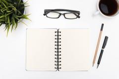 打开在白色书桌上的螺旋空白的笔记本 库存照片