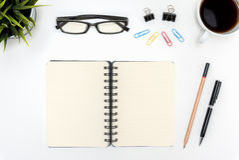 打开在白色书桌桌上的螺旋空白的笔记本 免版税库存照片