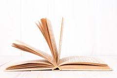 打开在白色木背景的书 库存照片