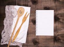 打开在线的笔记薄和有叉子的一把木匙子 免版税库存照片