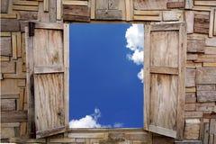 打开在蓝天和云彩看法的木窗口  库存图片