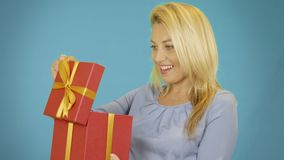 打开在蓝色背景的想知道的逗人喜爱的白肤金发的少妇红色礼物盒 影视素材