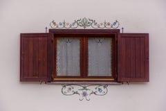 打开在装饰的白色墙壁上的木窗口 免版税库存图片