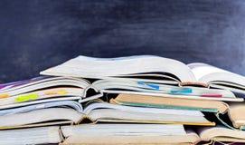 打开在黑板ba的桌上和课本堆积的精装书 免版税库存照片