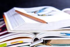 打开在黑板ba的桌上和课本堆积的精装书 库存照片
