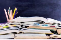 打开在黑板ba的桌上和课本堆积的精装书 库存图片