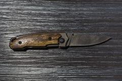 打开在黑木背景的被折叠的刀子 库存照片