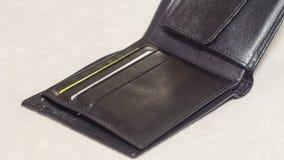 打开在轻的背景的黑皮革钱包 免版税库存照片
