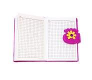 打开在紫色盖子的笔记本在白色背景 库存照片