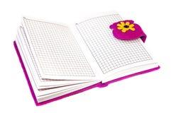 打开在紫色盖子的笔记本在白色背景 库存图片