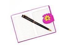 打开在紫色盖子的笔记本有在a的一支黑圆珠笔的 图库摄影