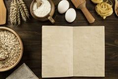 打开在年迈的木背景的老葡萄酒书 厨房器物,麦子,在罐的面粉的耳朵 免版税库存图片