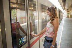 打开地铁门的美丽的少妇在驻地 图库摄影