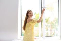打开大窗口的年轻美丽的妇女 免版税库存照片