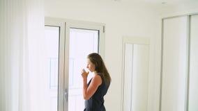 打开她的卧室帷幕和喝橙汁的妇女 股票录像