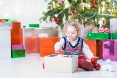 打开她的圣诞节礼物的小小孩女孩在一棵美丽的圣诞树下 免版税图库摄影