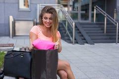 打开她的购物袋的女孩 销售的季节 库存照片