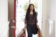 打开家运载的食品杂货袋的前门妇女 免版税库存照片