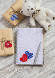 打开干净的笔记薄,在牛皮纸的自创情人节礼物,纸心脏,玩具涉及白色木桌 图库摄影