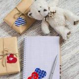 打开干净的笔记薄,在牛皮纸的自创情人节礼物,纸心脏,玩具涉及白色木桌 库存图片
