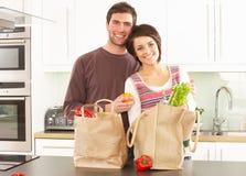 打开年轻人的夫妇厨房现代购物 免版税库存照片