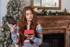 打开惊奇和欢欣的圣诞礼物的女孩 免版税库存图片