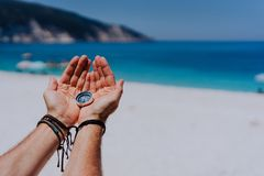 打开拿着金属指南针的手棕榈反对沙滩和蓝色海 搜寻您的方式概念 观点POV 图库摄影