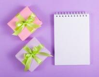 打开有一张空白页和两个礼物盒的笔记本在紫色背景 图库摄影