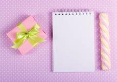 打开有一根空白页、华伦泰origami和蛋白软糖棍子的笔记本在圆点背景  免版税库存照片