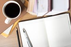 打开有书和咖啡杯的笔记本 免版税库存照片