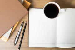 打开有书和咖啡杯的笔记本 免版税图库摄影