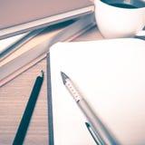 打开有书和咖啡杯葡萄酒样式的笔记本 免版税库存图片