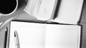 打开有书和咖啡杯黑白颜色的笔记本 免版税库存图片