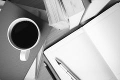 打开有书和咖啡杯黑白颜色的笔记本 免版税库存照片