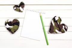 打开有军事心脏的空白的笔记本在白色木backgr 免版税库存照片